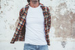 Man posing in blank white tshirt against street wal