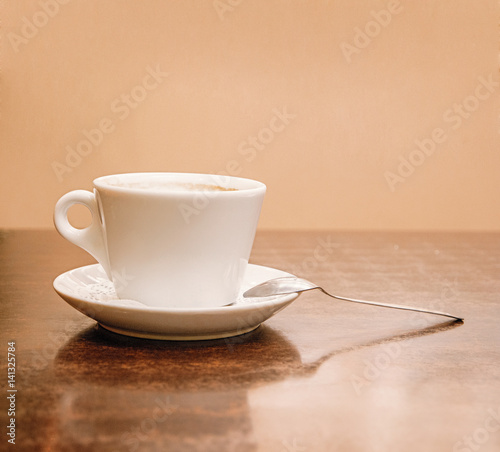 Coffee cup side view on wooden table. A lot of space for text on wall on background