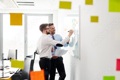Two businessmen working at office planning new strategy on whiteboard