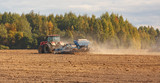 Sowing of crops on the field. Two tractors cultivate the soil on the field.