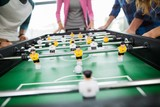 Mid section of executives playing table football