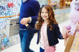 Smiley child shopping with parents at leisure