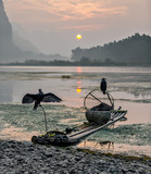 The ancient bamboo boat with cormorants and fishing net on the Li River at sunrise - Xingping, China