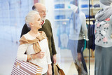 Senior couple with paperbags looking at clothes in display-window