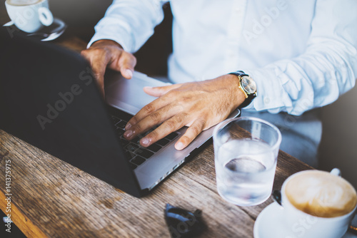Closeup shot of male hands typing on computer keyboard, professional businessman using modern laptop during a break at coffee shop, business and technology concept, filtered image