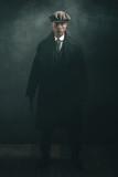Threatening retro 1920s english gangster holding gun in smoky room. - 141377591