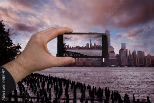 smartphone in hand photographing the night skyline of Manhattan - these are all photographs made by me, which separately can be found on my portfolio fotolia