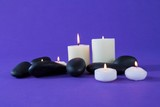 Candles and zen stones on purple background