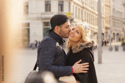 Poster mann küsst eine frau in der stadt