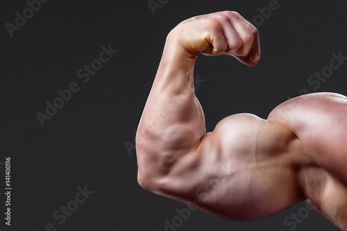 bodybuilding naked male arm with biceps on grey background