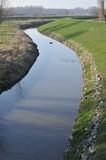Fertiggestellte Sanierung eines Hochwasserdeiches am Fluss mit Steinlage auf Textilvlies