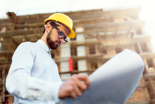 Architect at Construction Site Checking Blueprints