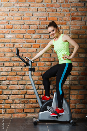 Poster Active woman using exercise bike at the gym.