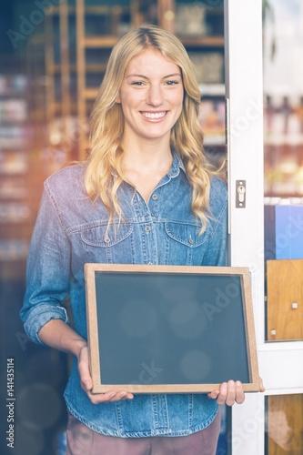 Smiling owner holding open signboard in supermarket