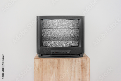 Poster Old Black TV with screen noise on a wooden shelf, Isolated background