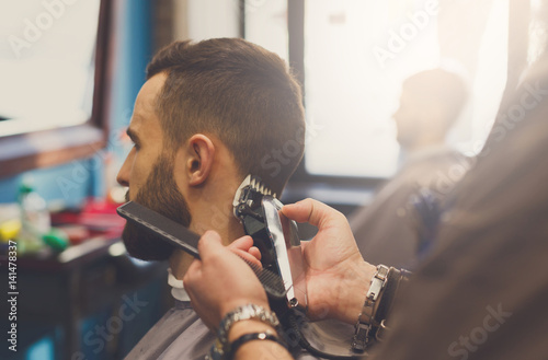 Man getting haircut by hairstylist at barbershop Poster