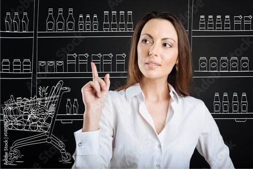 Pleasant concentrated woman buying in a supermarket