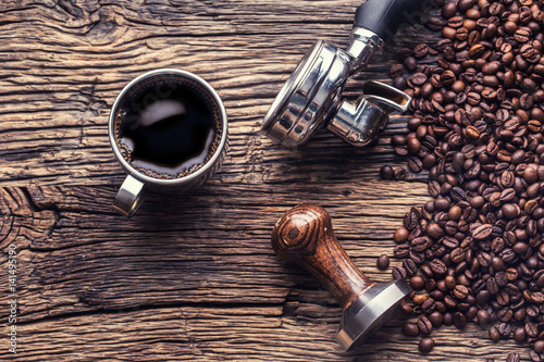 Coffee. Black coffee with coffee beans and portafilter on old oak wooden table.