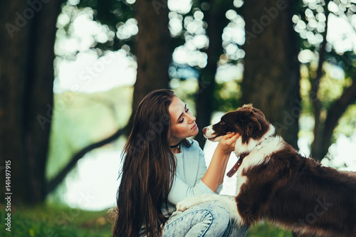 Poster Beautiful woman kissing her dog. Outdoor portrait.
