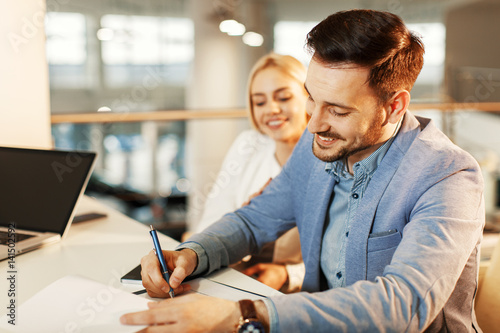 Young business couple signing a contract