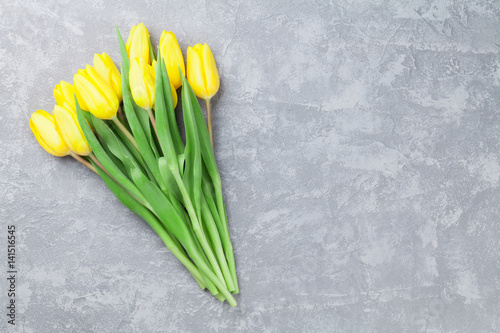 Easter card stone background with yellow tulips