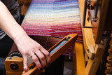 Hand of a woman weaving woven fabric on the weaving machine - 141517394