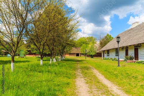 Rural road and old traditional house with straw roof in Tokarnia village on sunny spring day, Poland