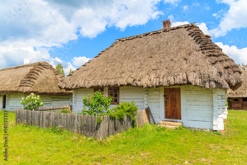 Old traditional house with straw roof in Tokarnia village on sunny spring day, Poland