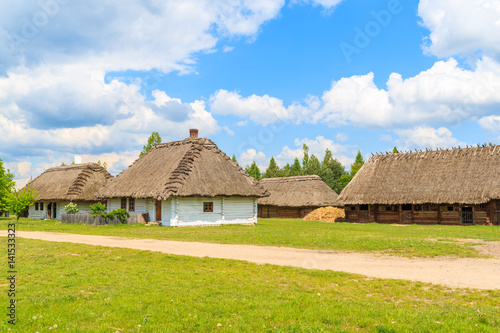 Rural road and old traditional houses with straw roof in Tokarnia village on sunny spring day, Poland