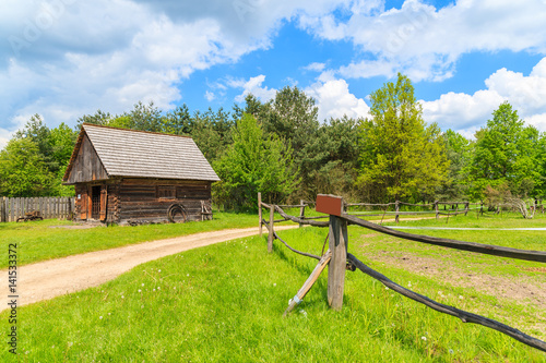 Rural road and wooden pasture fence in Tokarnia village on sunny spring day, Poland