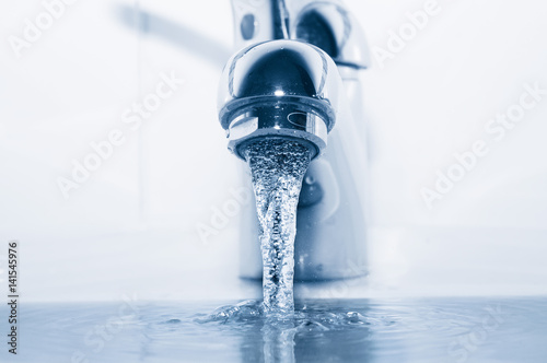 Faucet with flowing water closeup - 141545976