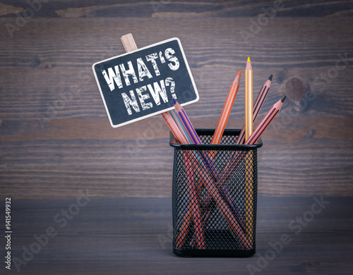 What's New. A small blackboard chalk and colored pencil on wood background.