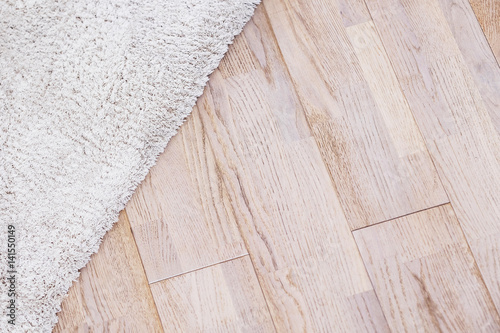 Podłoga laminowana parkietowa z beżowym miękkim dywanem