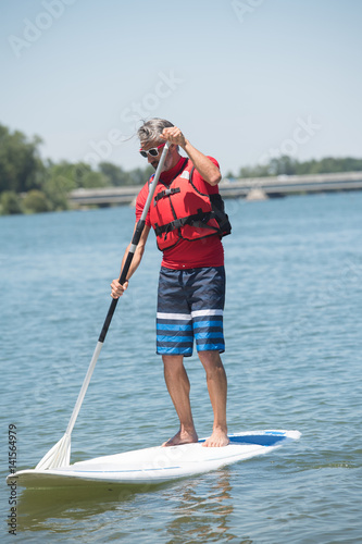 man enjoying a ride on the lake with paddleboard