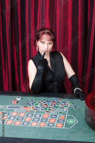 Plakat lass wearing  black gloves and black dress parlays in a casino