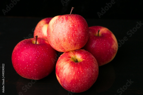 Red apples on black background. Wet. Close up