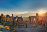 Particular of Ancient theatre of Taormina with Etna erupting volcano at sunset