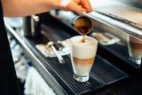 Close-up of barista preparing caffe latte