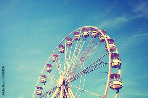 Vintage stylized picture of a Ferris wheel against the blue sky.