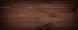 Dark brown scratched wooden cutting board. Wood texture background - 141606908