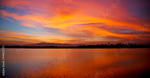 Foto op Canvas Crimson view from water of the sunrise full of colors