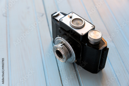 Poster top view of retro style camera on blue wooden table