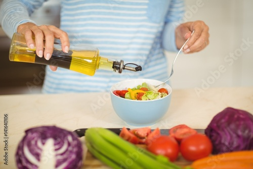 Woman pouring oil in to a bowl of vegetable salad