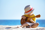 Fototapety Little boy plays guitar ukulele at sea beach