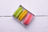 Multicolored macaroons on a white wooden table, top view.