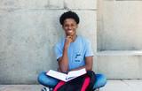 Fototapety Lachender Afrikaner beim Lernen