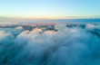 Beautiful aerial view of the clouds above the city during sunset.