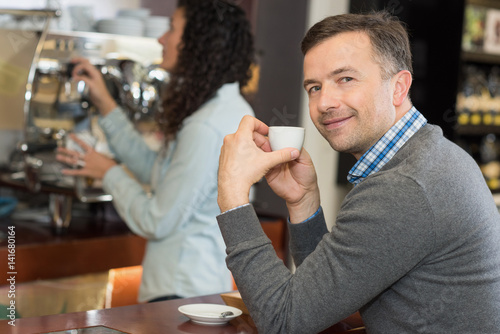posing with a cup of coffee