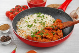 Frying pan with tasty chicken tikka masala and rice on wooden table