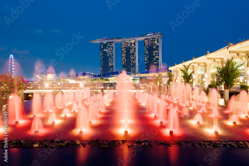 Marina Bay Sands and a colorful fountain at night in Singapore.